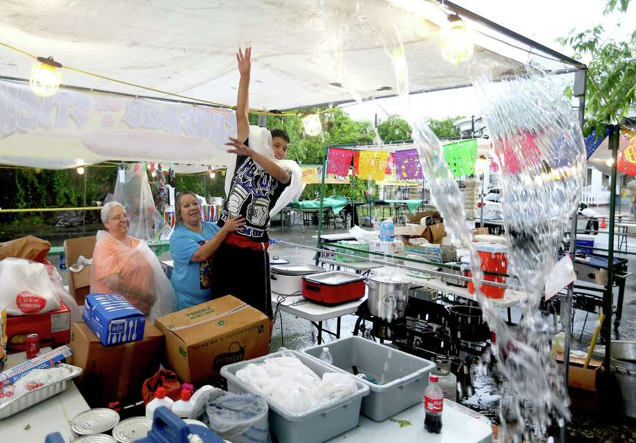 The Robles family drains rainwater off the tarp covering their sausage-on-a- stick booth near the VFW No. 76 Hall as they prepare for the Fiesta parades. Photo: William Luther / San Antonio Express-News / © 2016 San Antonio Express-News