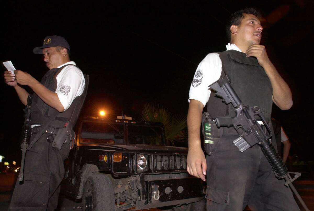 Tamaulipas state police officers stand guard in front of a police station in the border city of Matamoros, Mexico, late Thursday, June 21, 2001, where a raid by a group of armed men Tuesday freed a man held for questioning. While authorities assured residents that Tuesday's assault was an isolated incident, it gave a sobering peek at the strength of organized crime in this border city, where such Mafia violence has become rare since the fall of reputed kingpin Juan Garcia Abrego.