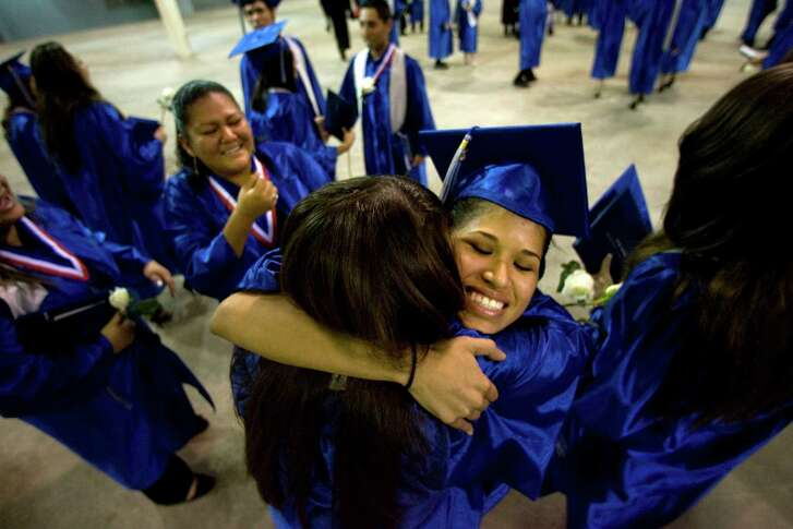 A Cesar E. Chavez High School student celebrates with her classmates after their graduation ceremony held at then-Reliant Arena.