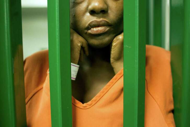 A female inmate peers though bars in an acute mental health cell block at the Harris County Sheriff's Office Mental Health Unit.  (Houston Chronicle file photo)