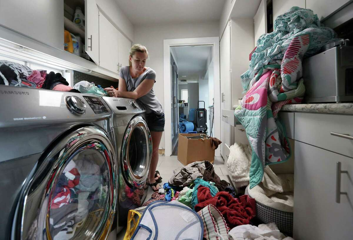 Erin Anders pauses to look at her belongings in the laundry room of her flood-damaged Meyerland home Thursday, April 21, 2016, in Houston. The home has flooded twice in the last year, and Anders cannot afford to rebuild or raise the house. ( Jon Shapley / Houston Chronicle )