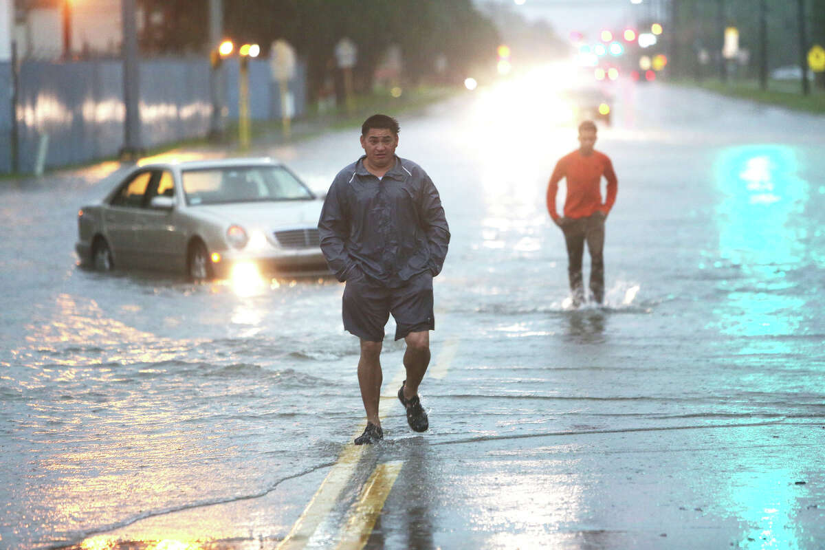 How the disaster unfolded Monday Morning: The degree of flooding only became fully known as daylight broke over the region Monday. Two men walk out of high water near Greens Bayou and Greens Rd., Monday, April 18, 2016, in Houston.