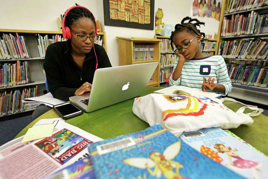 Sane'e Bell works on her computer as her daughter, Paige Bell, 6, reads from a stack of books she collected at the Harris County Library. Photo: Melissa Phillip, Staff / © 2016 Houston Chronicle