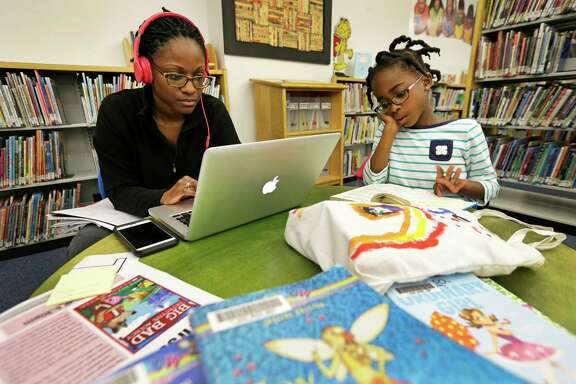 Sanee Bell works on her computer as her daughter, Paige, 6, reads from a stack of books she collected at the Harris County Library.