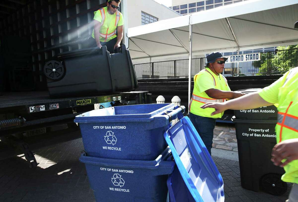 Solid waste workers place recycling containers and waste bins in Alamo Plaza as they make their way along the downtown parade route on April 21, 2016.