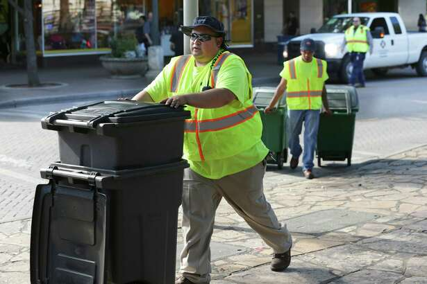 Workers place recycling containers and waste bins in Alamo Plaza in April. A reader comments on fines for placing trash in recycling bins.