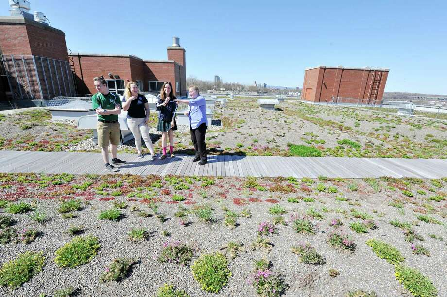 Students at The Doane Stuart School, senior Dan Sausto, left, junior Jackie LeBlanc, second from left and senior Maurin O'Connor, third from left, talk with Head of School Pam Clarke on the schools's green roof on Wednesday, April 20, 2016, in Rensselaer, N.Y.  The roof has 60,000 individual plants covering the 22,000 square-feet of space.  (Paul Buckowski / Times Union)