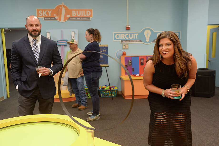Justin and Kelly Jackson watch as a science experiment involving Newton's laws is enacted at the Beaumont Children's Museum 4th annual Share the Magic Gala Thursday night. Event-goers were treated to the magic of illusionist Kyle Ryan while noshing on edibles from the Green Light Kitchen and taking in the museum highlights, science experiments, and a silent auction. Photo taken Thursday, April 21, 2016 Kim Brent/The Enterprise Photo: Kim Brent / Beaumont Enterprise