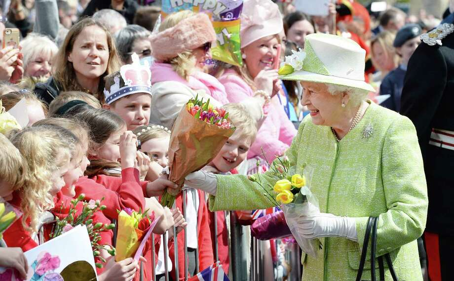 Britain's Queen Elizabeth II greets wellwishers, some with her favored flower, during a 'walkabout' on her 90th birthday in Windsor on Thursday.  Photo: JOHN STILLWELL, Staff / AFP or licensors
