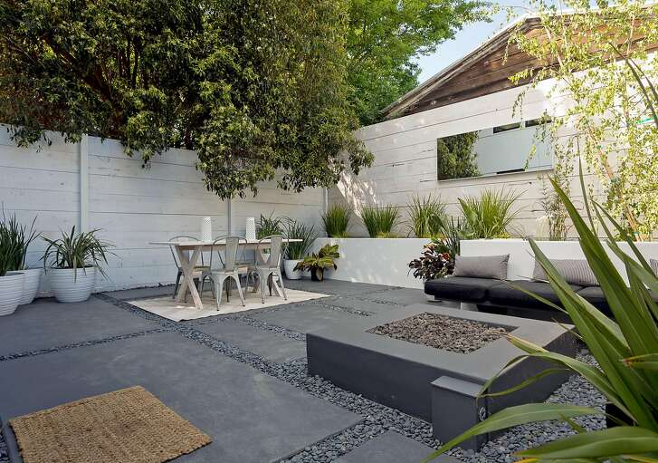 The great room opens to a hardscaped rear patio with a fire pit and raised planting bed.