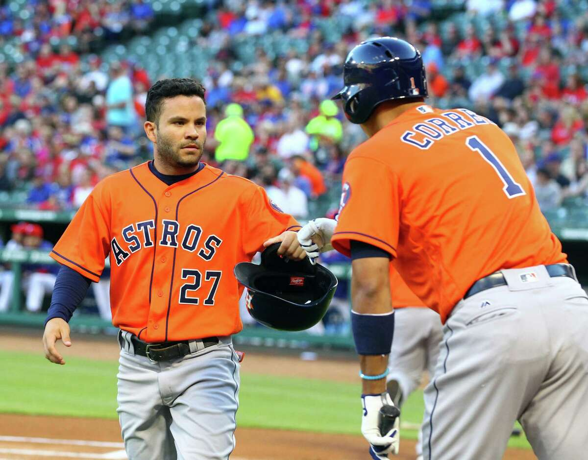 The Houston Astros' Jose Altuve (27) fist-bumps Carlos Correa (1) after Altuve scores on a double by George Springer in the first inning against the Texas Rangers at Globe Life Park in Arlington, Texas, on Thursday, April 21, 2016.