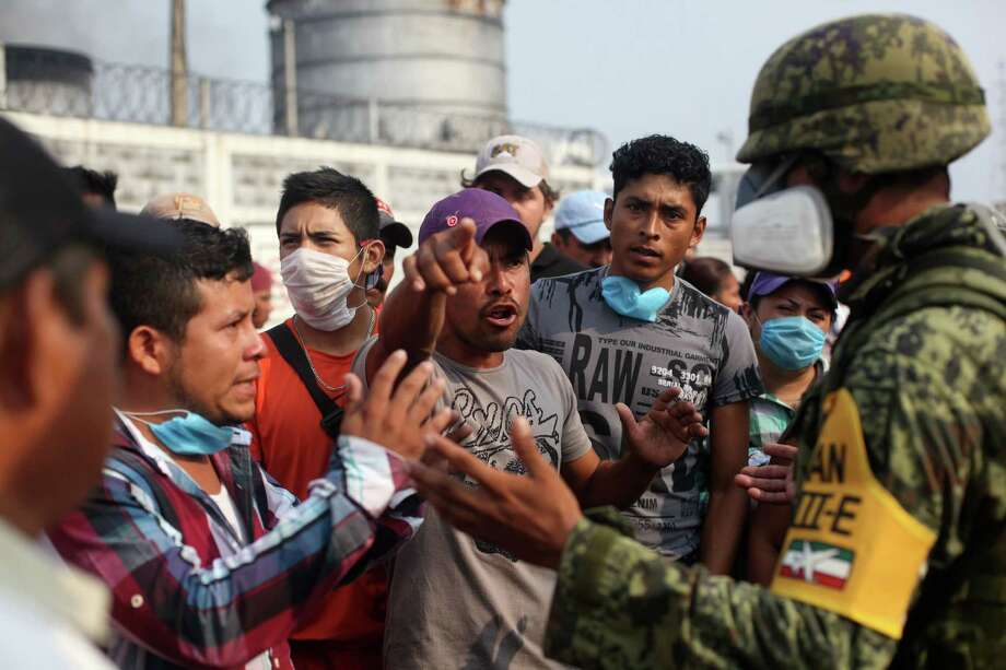 A relative of a missing worker argues with a Mexican soldier this week as he demands to be allowed to get more information about the petrochemical blast. Photo: Felix Marquez, STR / AP