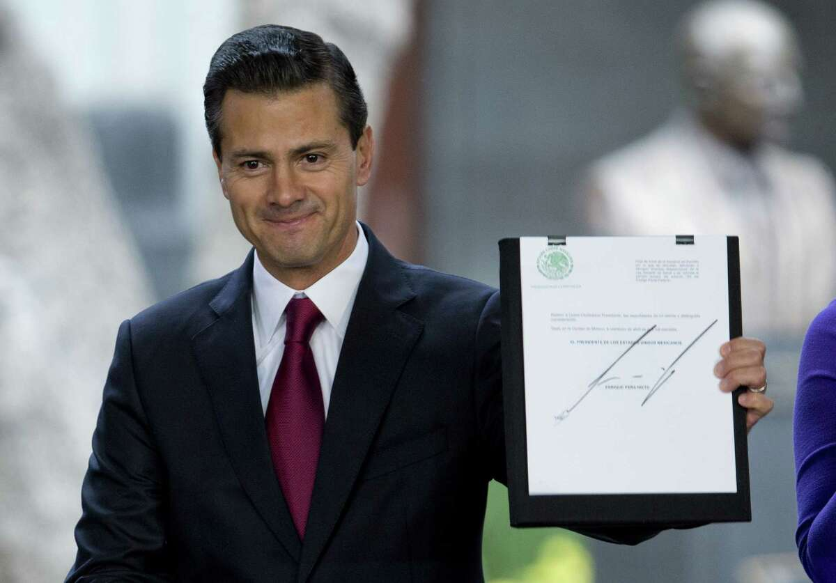 Mexican President Enrique Pena Nieto holds up a signed document during an announcement on proposed marijuana policy, in Mexico City, Thursday April 21, 2016. (AP Photo/Eduardo Verdugo)