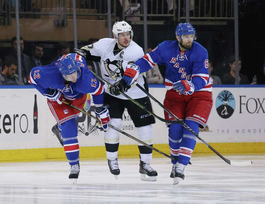 NEW YORK, NY - APRIL 21: Sidney Crosby #87 of the Pittsburgh Penguins goes up against Eric Staal #12 and Rick Nash #61 of the New York Rangers during the third period in Game Four of the Eastern Conference First Round during the 2016 NHL Stanley Cup Playoffs at Madison Square Garden on April 21, 2016 in New York City. The Penguins defeated the Rangers 5-0.  (Photo by Bruce Bennett/Getty Images) ORG XMIT: 629101653 Photo: Bruce Bennett / 2016 Getty Images