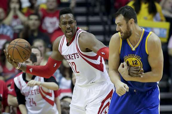 Golden State Warriors center Andrew Bogut, right, fouls Houston Rockets center Dwight Howard during the first half in Game 3 of a first-round NBA basketball playoff series, Thursday, April 21, 2016, in Houston. (AP Photo/David J. Phillip)
