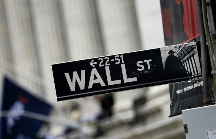 FILE - This Oct. 2, 2014, file photo, shows a Wall Street sign adjacent to the New York Stock Exchange. Global stocks were mostly higher Thursday, April 21, 2016, after U.S. stocks were lifted by an uptick in oil prices. A weakening of the Japanese yen pushed Tokyo's benchmark 2.7 percent higher. (AP Photo/Richard Drew, File)