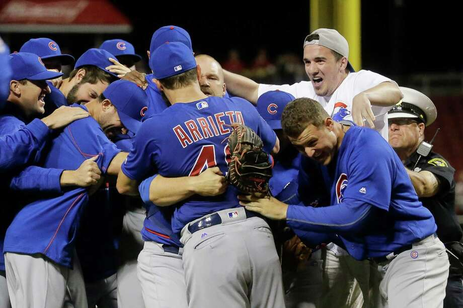 A fan, top right, who ran onto the field celebrates with Chicago Cubs starting pitcher Jake Arrieta (49) and his teammates after Arrieta throw a no-hitter against the Cincinnati Reds in a baseball game, Thursday, April 21, 2016, in Cincinnati. The Cubs won 16-0. (AP Photo/John Minchillo) Photo: John Minchillo, STF / AP
