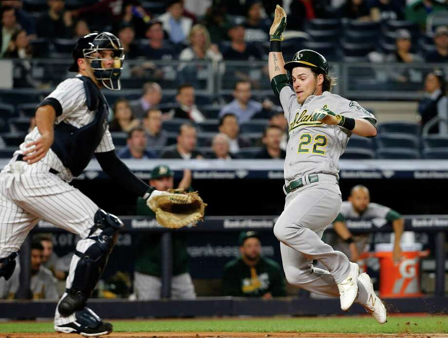 New York Yankees catcher Brian McCann (34) waits for a throw as Oakland Athletics' Josh Reddick (22) scores on Jed Lowrie's fourth-inning single in a baseball game in New York, Thursday, April 21, 2016. (AP Photo/Kathy Willens) ORG XMIT: NYY103 Photo: Kathy Willens / Copyright 2016 The Associated Press. All rights reserved. This m