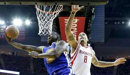 Golden State Warriors forward Draymond Green, left, shoots around Houston Rockets forward Michael Beasley during the second half in Game 3 of a first-round NBA basketball playoff series, Thursday, April 21, 2016, in Houston. (AP Photo/David J. Phillip)