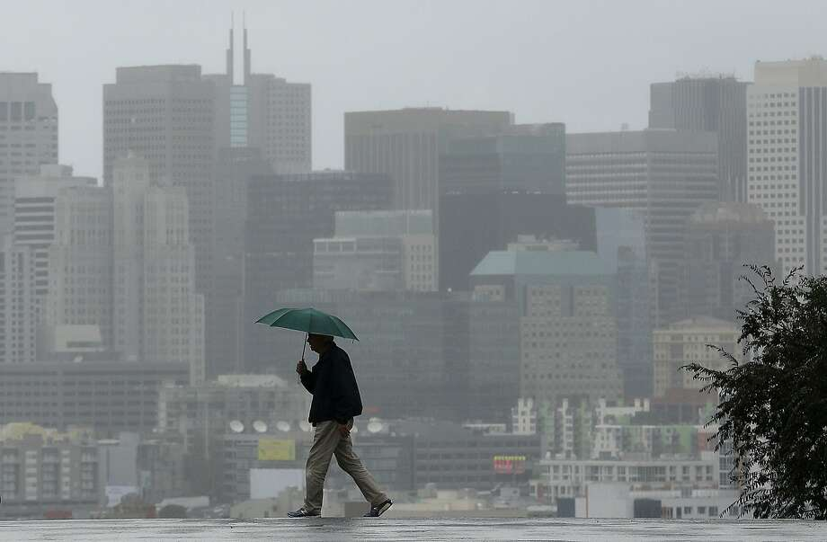 In this Jan. 5 file photo, Richard Polich holds an umbrella as he crosses a street in the rain in San Francisco. More rain is expected for the Bay Area beginning late Thursday. Photo: Jeff Chiu, AP