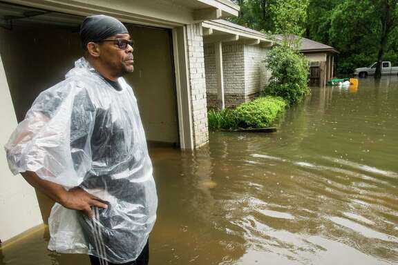 Craig Baldwin pauses outside his house while trying to clean up after the home was flooded in the Timber Lakes Timber Ridge subdivision on Monday, April 18, 2016, south of The Woodlands, Texas. More than a foot of rain fell Monday in parts of Houston, submerging scores of subdivisions and several major interstate highways, forcing the closure of schools and knocking out power to thousands of residents who were urged to shelter in place. (Brett Coomer/Houston Chronicle via AP)