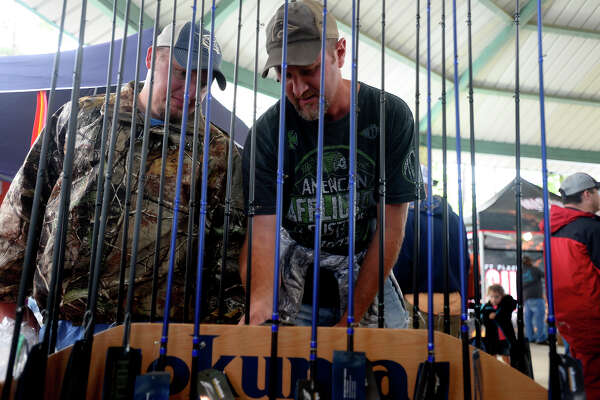 Richard Cooper, left, and Jason Davis, both of Jacksonville, Texas, look at fishing rods on sale at Okuma High Performance's booth at the Big Bass Splash on Lake Sam Rayburn in Jasper on Thursday.  Photo taken Thursday 4/21/16 Ryan Pelham/The Enterprise
