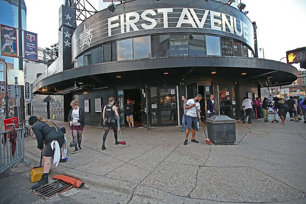 First Avenue staff clean up the outside of the building after fans gathered outside the night before to honor Prince in Minneapolis, on Friday, April 22, 2016. Prince, widely acclaimed as one of the most inventive and influential musicians of his era with hits including