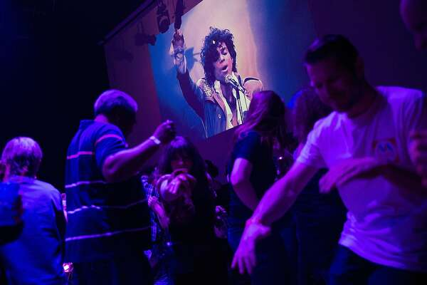 Guests dance to Prince music as a slide show flashes images of the artist above the stage during a memorial dance party at the First Avenue nightclub on April 21, 2016 in Minneapolis, Minnesota. Prince, 57, was pronounced dead shortly after being found unresponsive at Paisley Park Studios in Chanhassen, Minnesota near Minneapolis.