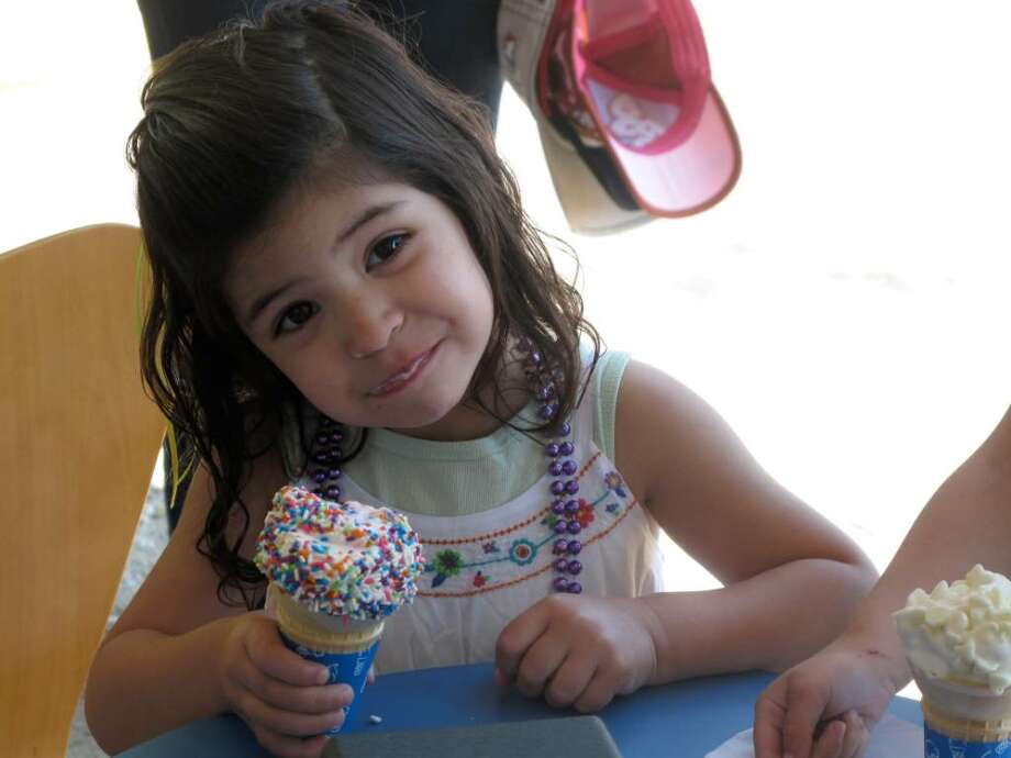 """Samantha Handler, 3 1/2, tests out Tasti D-Lite's vanilla cone with rainbow sprinkles during its three-hour long """"Free Sample"""" event on Wednesday. The frozen treat shop officially opens today at 380 Heights Road in Darien. Photo: Maggie Gordon / Darien News"""