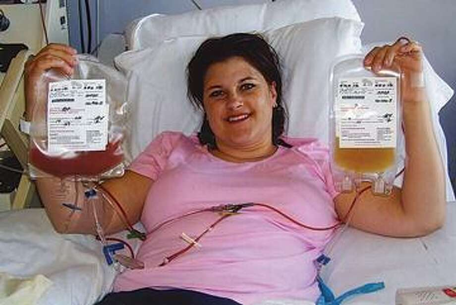 Staci Zimmerman holds up the bag of blood stem cells she donated.