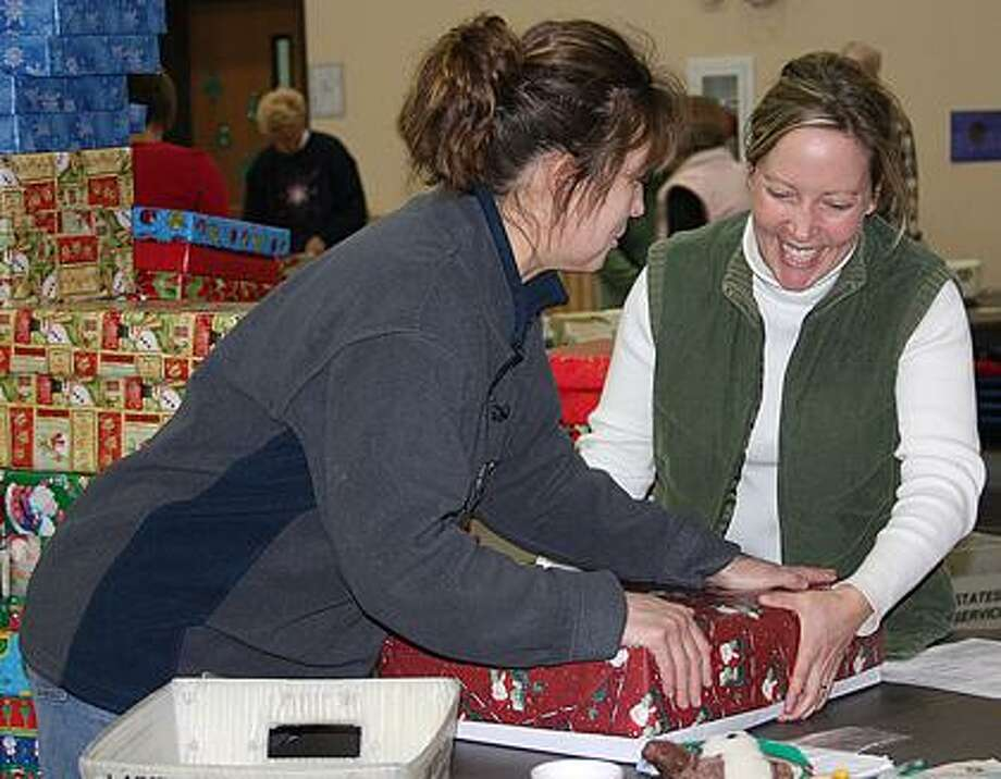 Cherie Andrich and Carrie Sorenson wrap gifts.