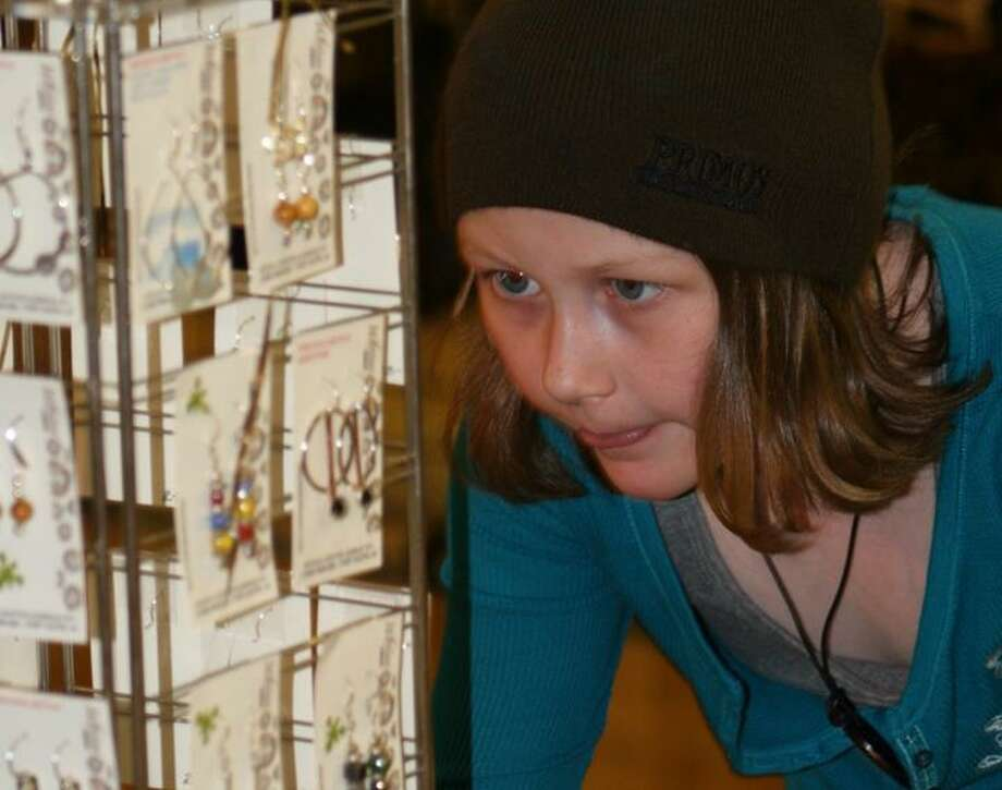 Abbi Drews, 9, of Bad Axe, looks intently at jewelry created by Lynne Wiencek, of Port Austin, owner of Whim Originals.