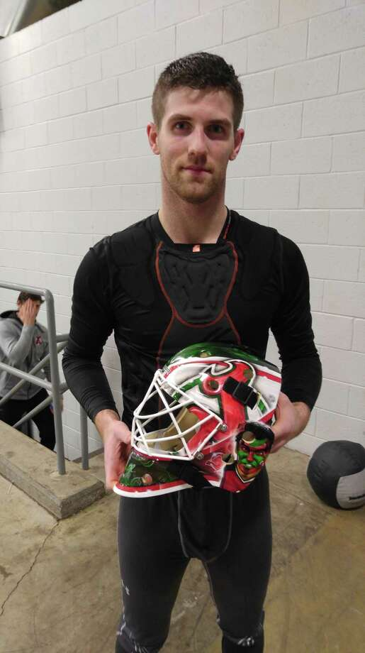 Albany Devils goaltender Scott Wedgewood holds his mask, which features a portrait of the Seinfeld character David Puddy, who was a huge New Jersey Devils fan in the series. (Pete Dougherty/Times Union)