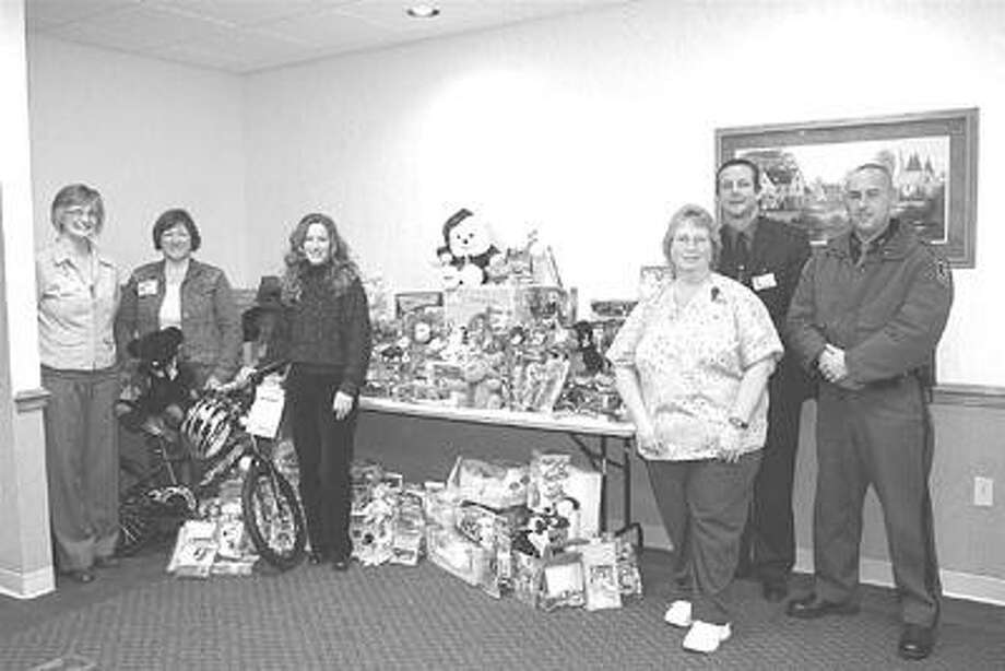 Pictured are Trooper Brian McComb from the Bad Axe post and Scheurer Healthcare Network employees, Rhonda Buehler, Colleen Braun, Sandee Henderson, Greg Foy and Diane Diebel, with the toys donated by employees of Scheurer Healthcare Network.