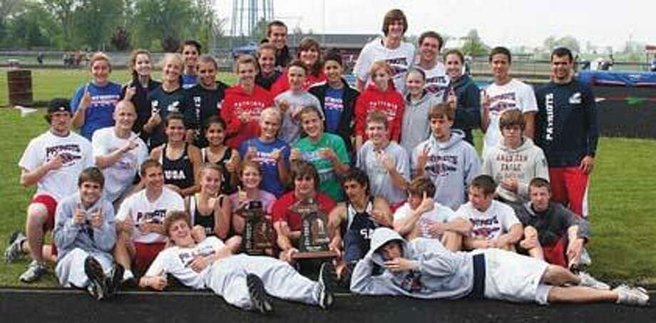 USA boys and girls track teams pose with trophies.
