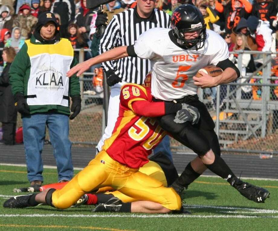 Ubly quarterback Jordan Kaufman is brought down by Reading's James Piner. Ubly won the semifinal game Saturday, 47-8.