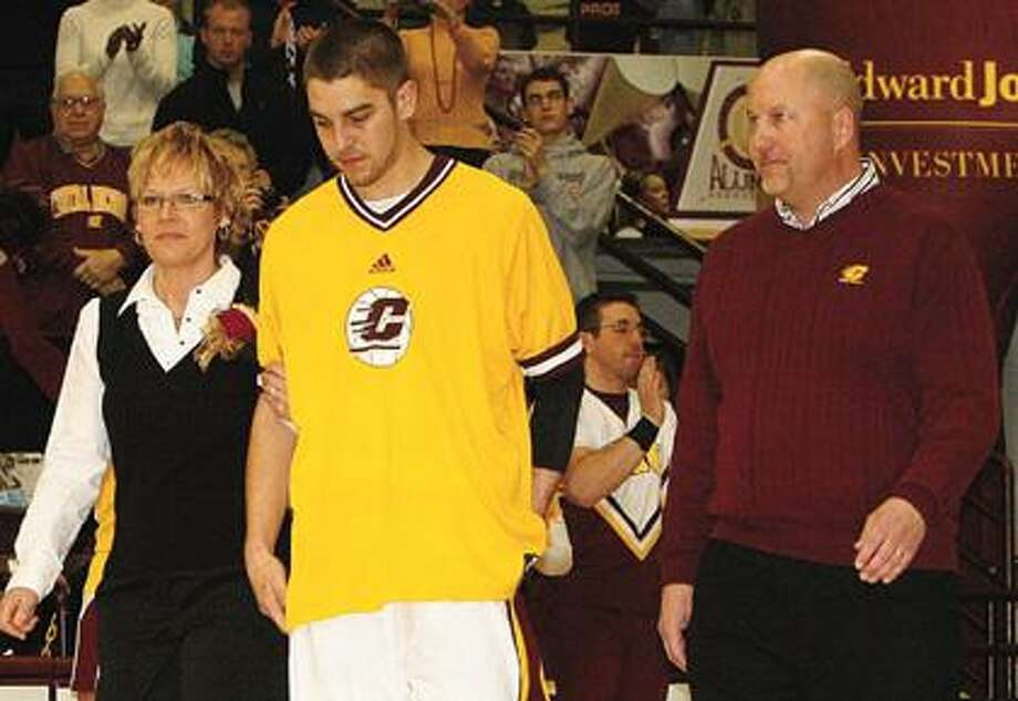 Central Michigan's Jordan Bitzer is escorted by his parents, Scott and Kim Bitzer, on Saturday prior to the start of a game with Western Michigan.