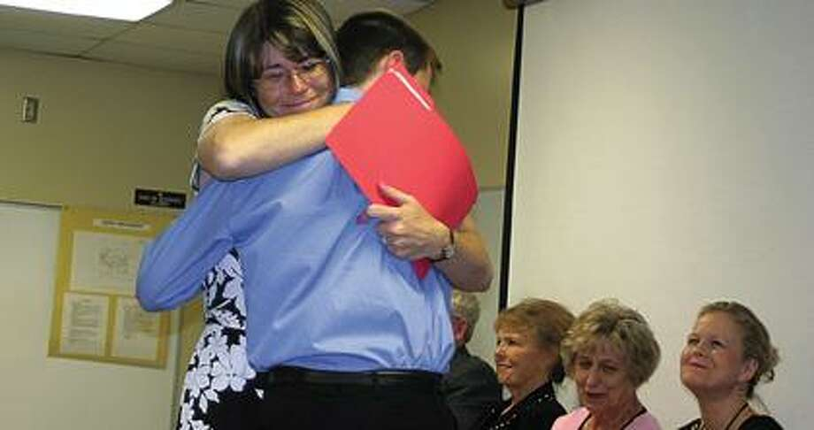 Teacher Anne Kennedy gives a graduate a hug.