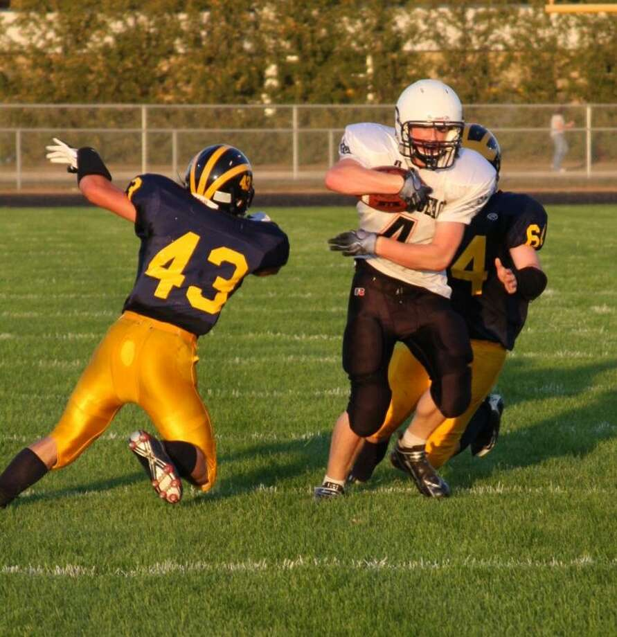 Harbor Beach's Ryan Maurer eludes the tackle from Bad Axe's Philip Delpiere (64) and Charlie Becking on Friday night.