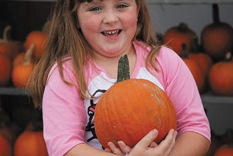 Carrying a pie pumpkin is Emily Smith, 5, of Caseville,