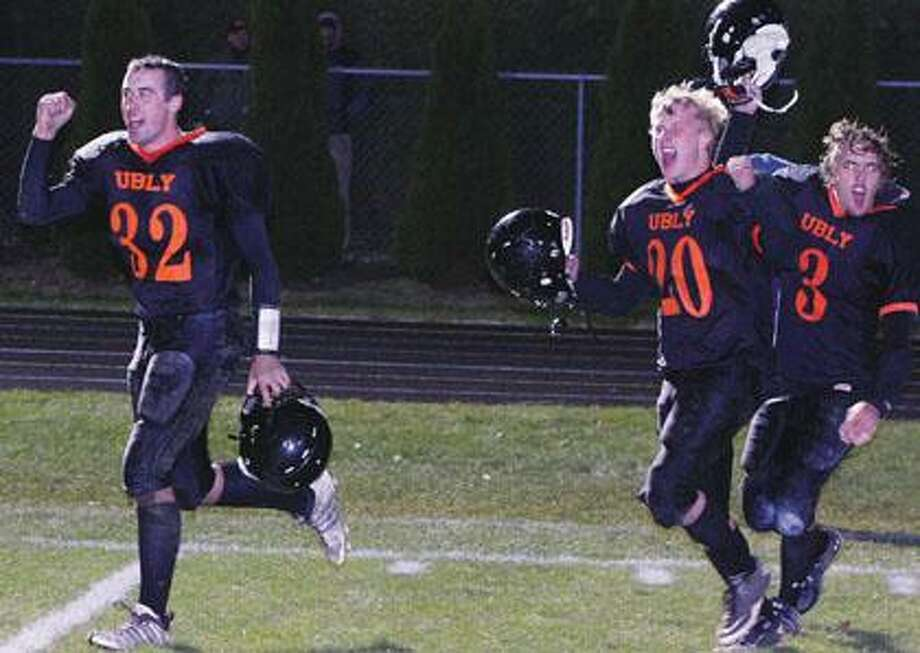 Seniors Eric Booms (32), Tyler Peruski (20) and Bryan Nash (3) celebrate last week's district championship win over Saginaw Nouvel.