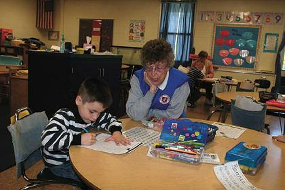 Nettie Whear helps kindergartner Cole Hartman.