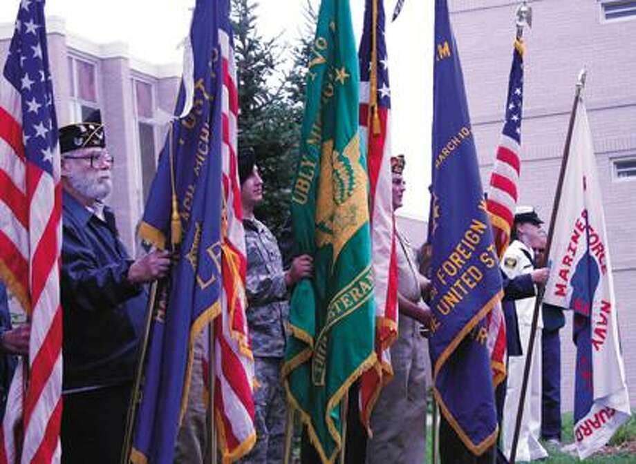 Veterans hold U.S. flags and flags representing their post.