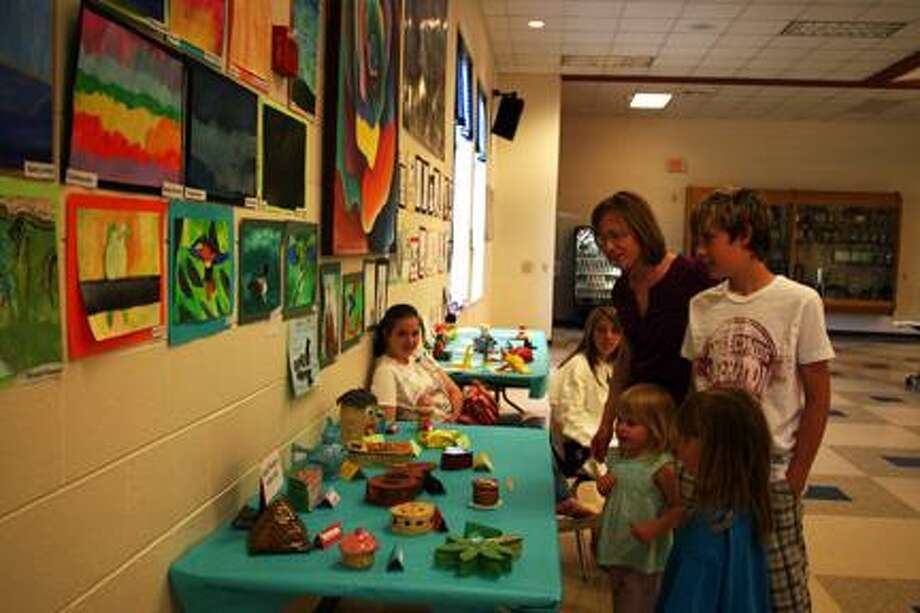 Doris Wisneski of Kinde, fifth-grader Anthony Wisneski, kindergartner Olivia Cox and 3-year-old Emma Cox looks at the art on display.