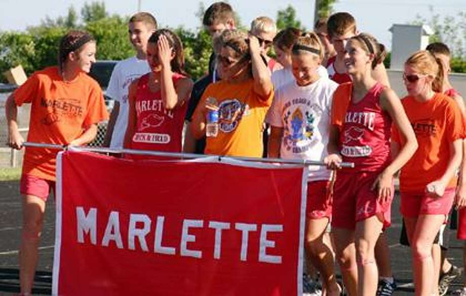 Members of the Marlette boys and girls track team march into the Caro Meet of Champions bearing the school colors.