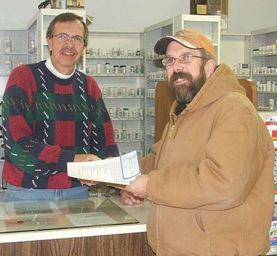 Marlette's Roger Ballard presents checks to Marlette pharmacist Rudy Bolf to send one WWII veteran to the 2011 excursion to visit the WWII Memorial in Washington D.C.