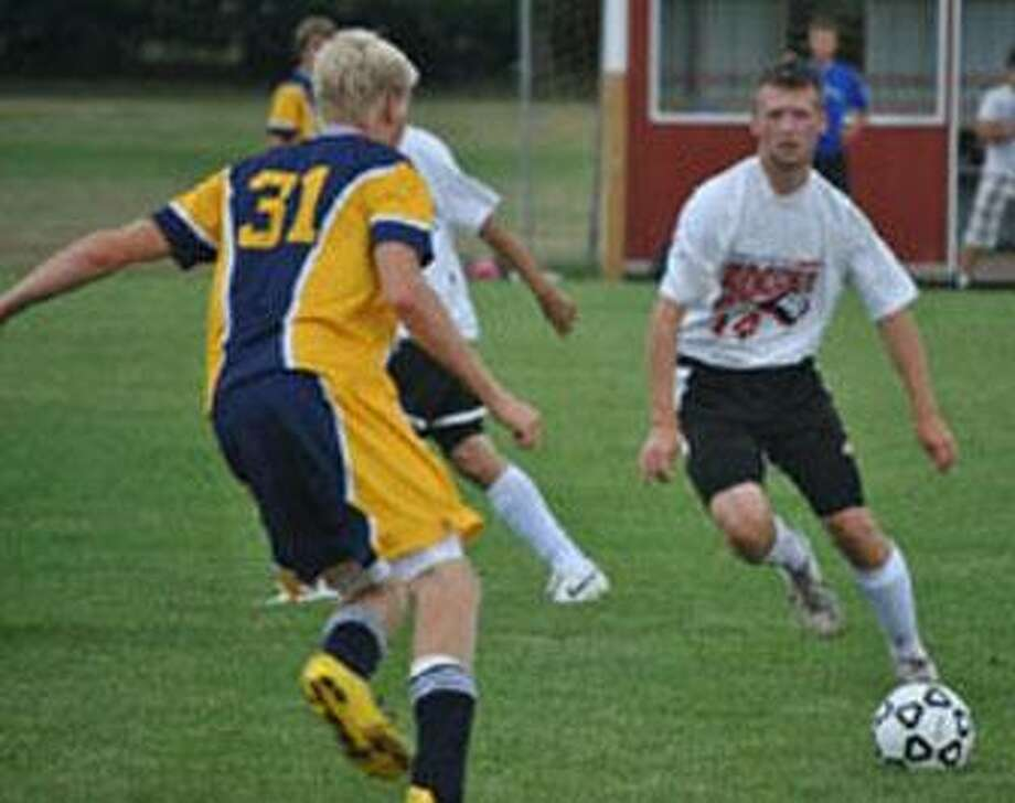 Marlette's senior midfielder Brent Speer drives the ball downfield during Marlette varsity soccer action August 23rd in Marlette. Speer and a Bad Axe player were later injured and the game was called with some five minutes remaining resulting in a 0-0 tie.