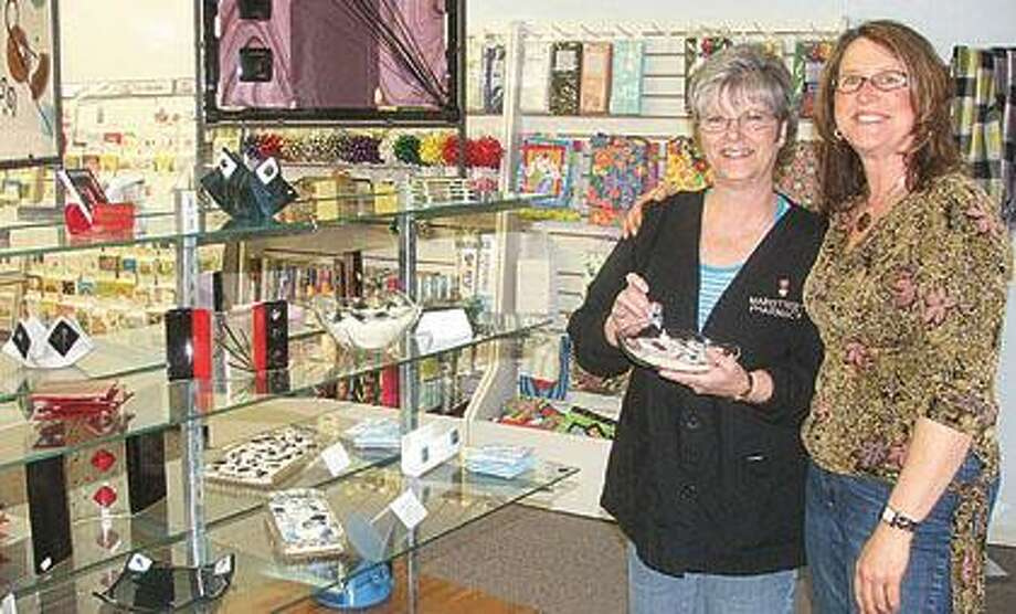 Marlette's Arlene Wilkinson of Arlene Wilkinson's Creations In Glass, right is joined by Mainstreet Pharmacy employee Marilyn Herron in the new section of the local pharmacy which is featuring the talents of local artists. Here, Herron displays a piece of jewelry as the couple is surrounded by selections of Wilkinson's beautiful glass creations.