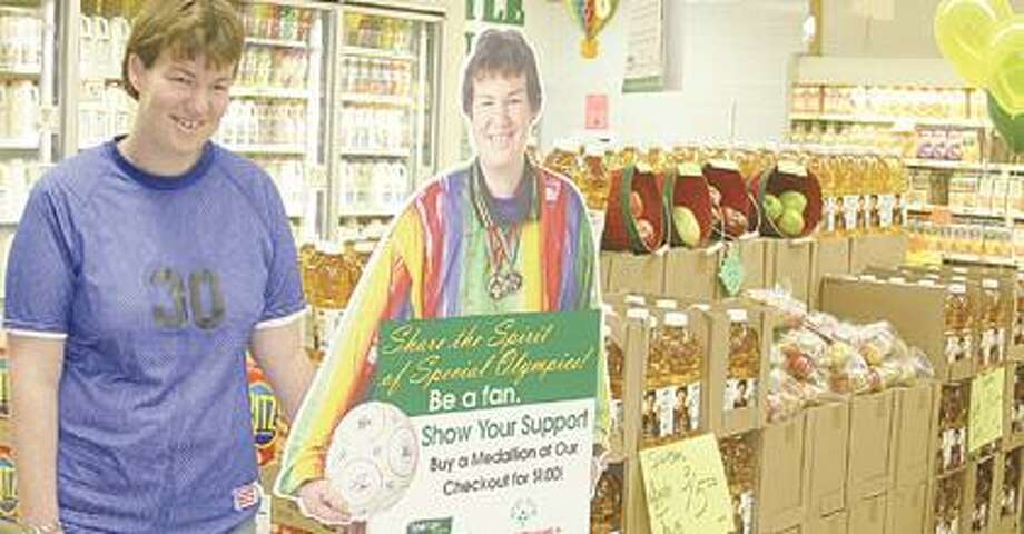 Melissa Prill, 2007 Inspirational Athlete Award recipient by Special Olympics Michigan, is pictured here next to a cut-out of the picture that's on Spartan apple juice bottles.