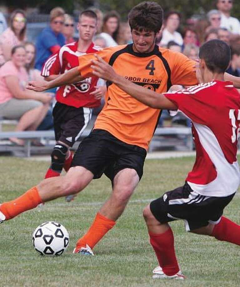 Harbor Beach's Dustin Mazure (4) works against Marlette's Brandon Lucik (13) during the first half of the Pirates' 1-0 overtime win on Wednesday.